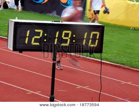 Finishing runner during a triathlon with stopwatch