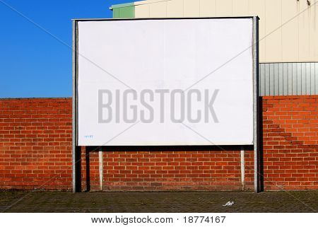 White billboard in front of a brickstone wall