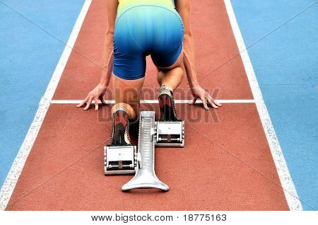 Starting runner in a starting block on an athletic track