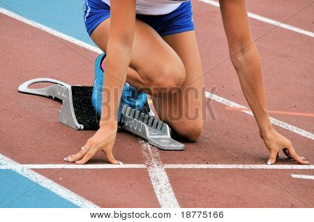Female athlete in starting position on an athletic track