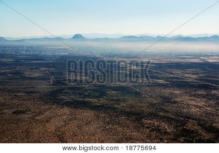 Aerial of desert towns Douglas, Arizona, on left, and Agua Prieta, Mexico, on right, in hazy weather, with dividing border fence