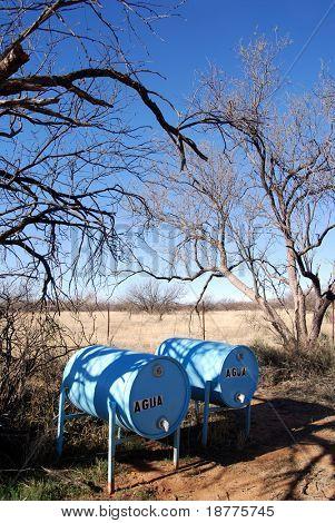 """Tanques de agua con la izquierda del texto """"agua"""" para los inmigrantes indocumentados en desierto"""