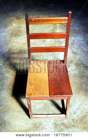 Simple wooden chair in a dark room illuminated by natural light from above
