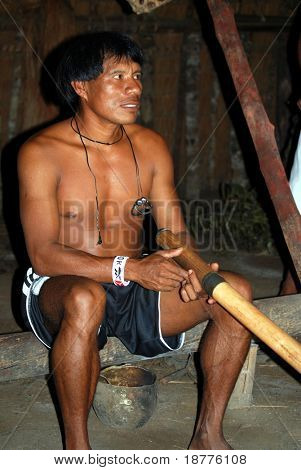 KAMAYURA VILLAGE, BRAZIL - MAY 18: Member of a threatened Indian tribe, the Kamayura, playing a sacred flute on May 18, 2008, in the Kamayura village.