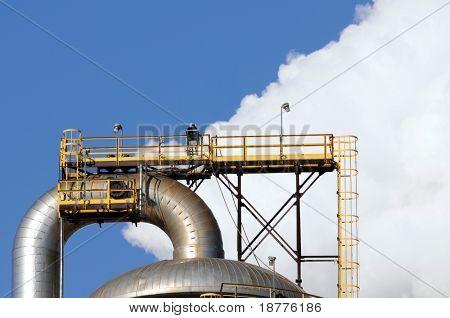 Closeup of smoke rising behind a distillation tower at a petrochemical plant