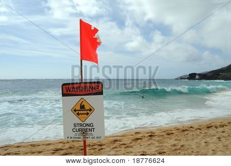 Red flag and warning sign on a dangerous beach in Hawaii. This particular sign was shot at Sandy Beach, a legendary bodysurfing location on Oahu, warning about strong currents.