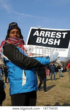 WASHINGTON - JAN 20: An unidentified demonstrator holds a sign demanding the arrest of U.S. President George Bush at the inauguration of U.S. President Barack Obama on January 20, 2009 in Washington.
