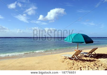 Two chairs and an umbrella on the beach in Waikiki Beach, Honolulu, Hawaii