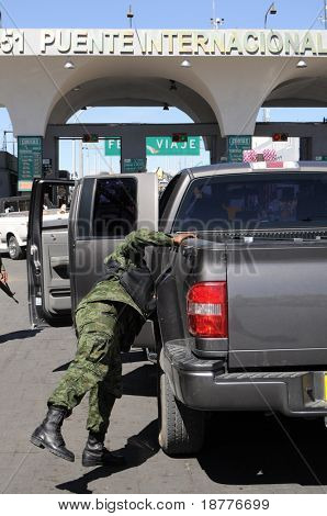 An army soldier checking vehicles traveling from Mexico to the U.S. on a checkpoint in Ciudad Juarez.
