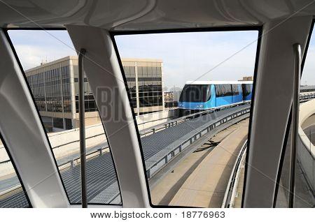 Un tren monorraíl moderna encontrando otro tren monorraíl en una pista elevada en un aeropuerto