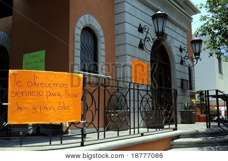Signs posted outside a restaurant in Mexico City informing that only takeout food is served because of a citywide shutdown imposed (shot April 30, 2009) to combat influenza epidemic.