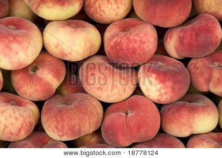 A background of fresh donut peaches for sale at a market. These peaches are also known as 'flat' or 'saturn' peaches