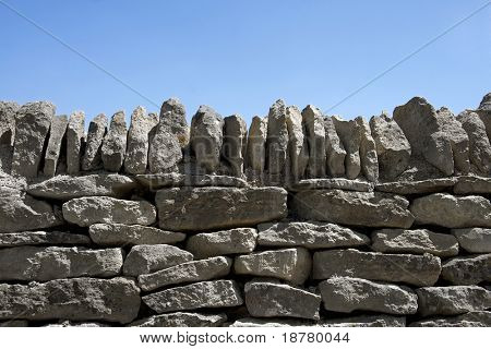 A dry stone wall against clear blue sky. Space for text.