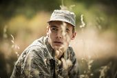 Thoughtful military soldier relaxing in grass in boot camp poster