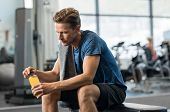 Young man in gym sitting alone opening a bottle of energy drink. Thoughtful fit man in gym holding f poster