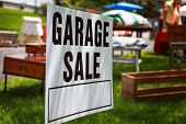 Garage sale sign on the shady lawn of a suburban home, shallow focus in center of sign poster
