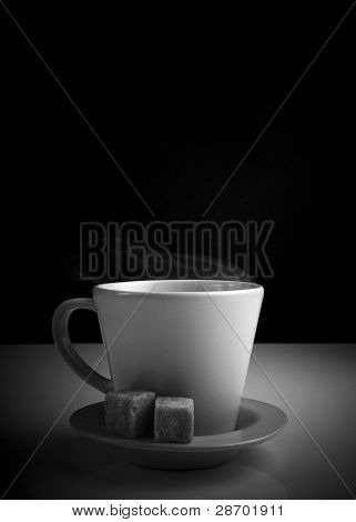 white cup of hot beverage b/w