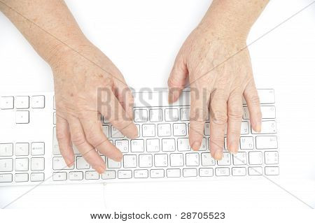 Hands Of An Old Female Typing On The Keyboard, Isolated On White, Close-up.