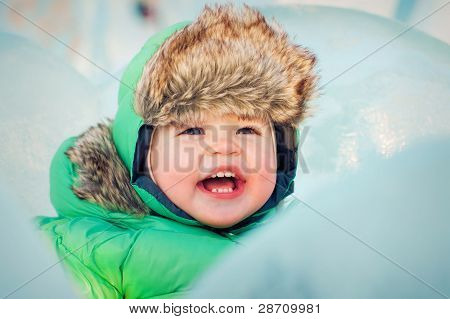 Cute Smiling Baby In Winter Clothes Near Ice Cube