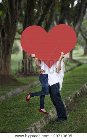 Couple Kissing Behind Heart Cutout