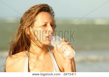 Woman Drinking Water On The Beach