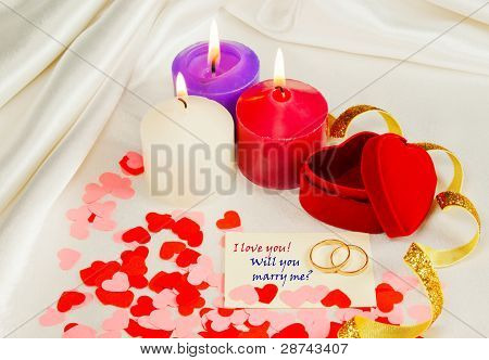 Two Rings And A Card With Marriage Proposal With Three Candles