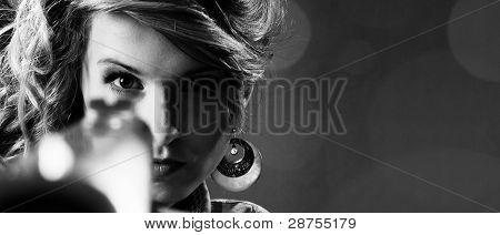 Attractive Girl Pointing A Gun. Closeup Portrait