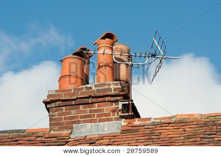 Clay Chimney Pots On Old Tiled Roof