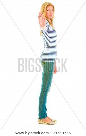 Full Length Portrait Of Serious Teen Girl Showing Stop Gesture