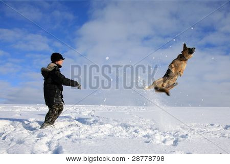 Boy and dog playing in snow