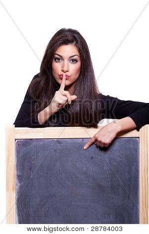 Keep It Secret. Woman Pointing At A Blank Blackboard