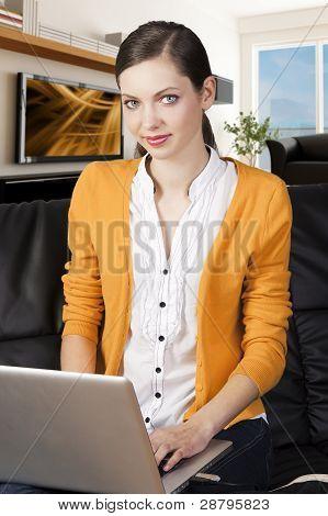 Mädchen auf Sofa mit Laptop, She der Lächeln und schauen Sie in das Objektiv