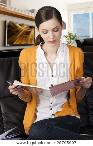 The Girl Reading A Book With A Pen In Her Right Hand