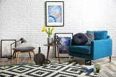 Modern Living Room Interior With Comfortable Armchair And Stool Near Brick Wall poster