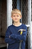image of chicken-wire  - Cute young holding a hammer in front of a chicken coop he helped repair - JPG