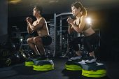 Group Of Healthy Fitness People In Gym, Young Couple Is Working Out At Gym, Attractive Woman And Han poster