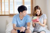Beautiful Young Asian Couple In Love Surprise Gift Box In Bedroom At Home, Family Anniversary With E poster