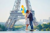 Loving Couple With Bunch Of Colorful Balloons Kissing Near The Eiffel Tower In Paris, France poster