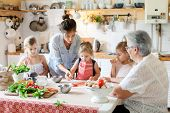 Family Are Cooking Italian Pizza Together In Cozy Home Kitchen. Cute Kids, Mother And Grandmother Ar poster