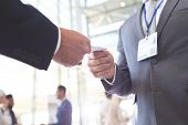 Close-up of diverse business people exchanging business card in conference poster