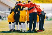 Coach Coaching Girls Sports Team. Girls School Sports Team Huddling With Coach On The Grass Field. S poster