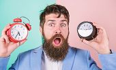 Man Bearded Hipster Hold Two Different Clocks. Guy Unshaven Puzzled Face Having Problems With Changi poster