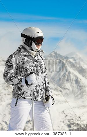 Young woman in ski suit and in helmet stands on background of mountains and blue sky