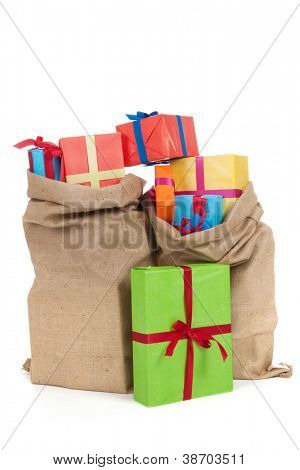 many colorful presents with luxury ribbons in jute bags isolated over white background