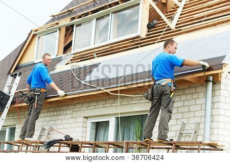 two workers on roof at works with flex tile material measuring roofing drain distance
