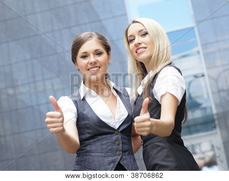 Two young attractive business women demonstrate the success