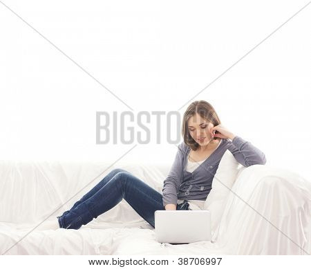 Young attractive girl with the laptop sitting and relaxing on the sofa