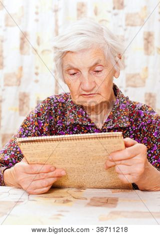 Elderly Happy Woman Read Something From The Book