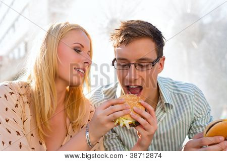 Couple is hungry and eating a burger at lunch time in the sun