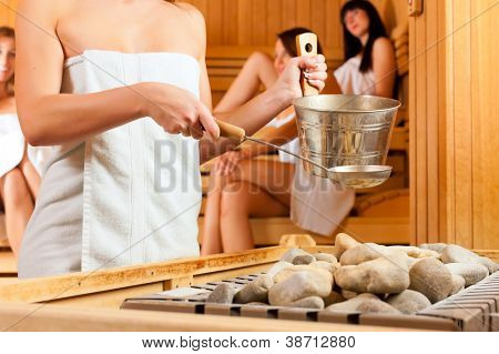 Wellness - young happy women in sauna of a Spa, water and scent are splashed on hot stones for steam